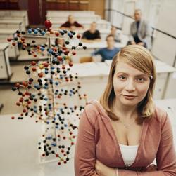 Female science teacher in classroom with model of a DNA helix in background